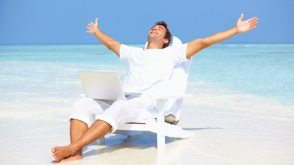 Portrait of carefree man outstretching his arms with laptop on beach