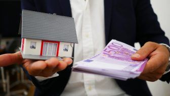 Person holding cash and a miniature house